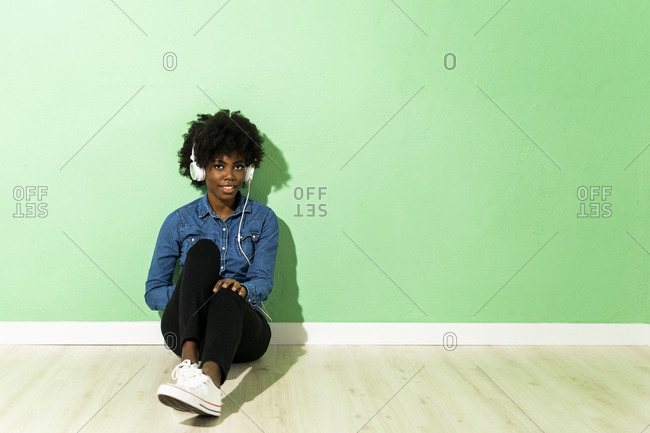 Young woman listening music through headphones while sitting on floor against green background