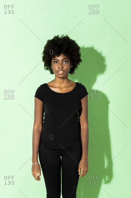 Young woman staring while standing against green background