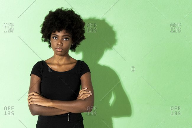 Young woman with arms crossed standing against green background