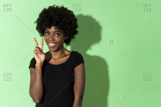 Smiling woman showing peace gesture while standing against green background