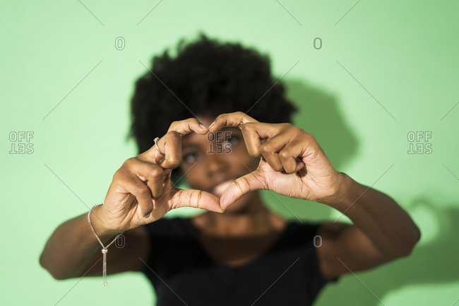 Young woman making heart shape with finger while standing against green background