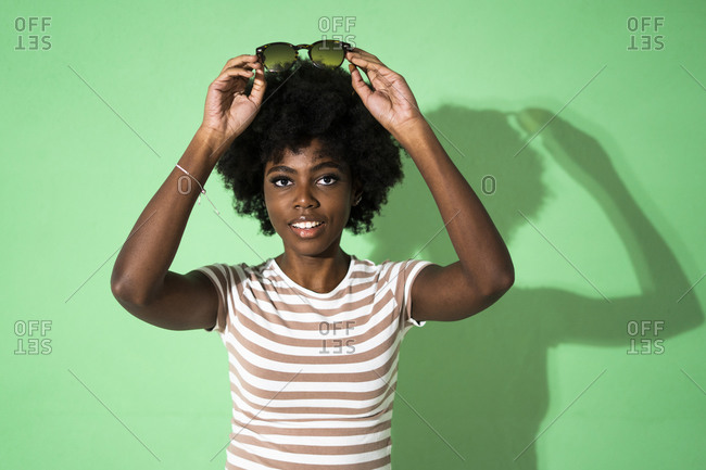 Woman wearing putting sunglasses on head while standing against green background