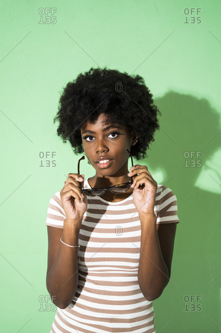 Young woman holding sunglasses while standing against green background