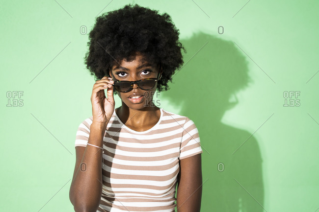 Woman with sunglasses staring while standing against green background