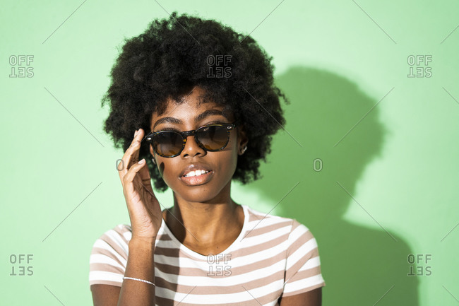 Woman adjusting sunglasses while standing against green background