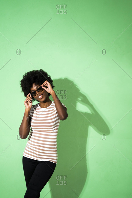 Young woman adjusting sunglasses while standing against green background