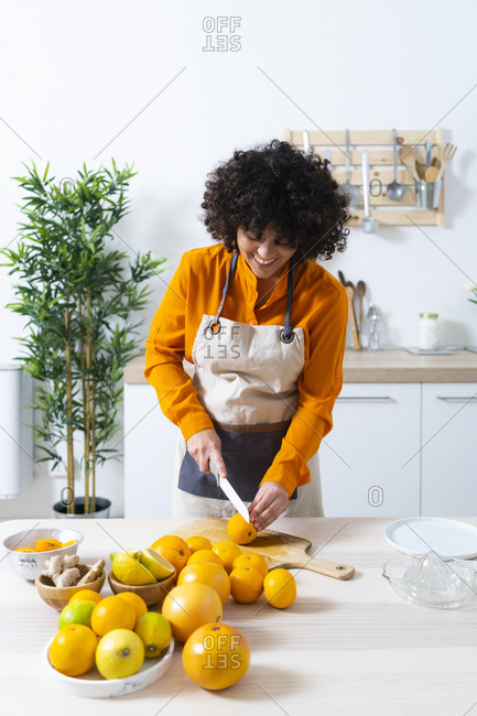Young woman cutting orange for making juice while standing in kitchen at home