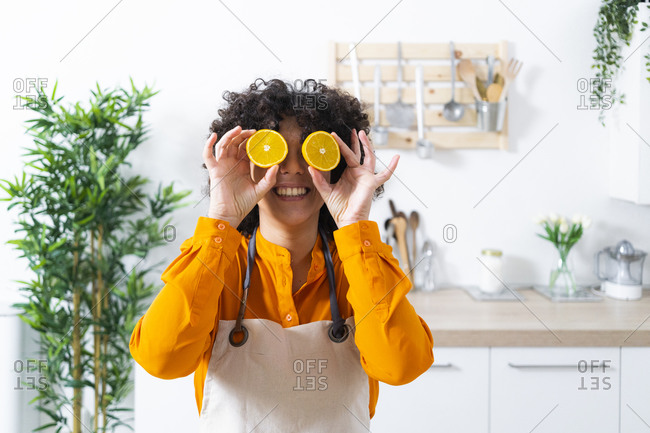 Playful woman covering eyes with slice of orange while standing at kitchen