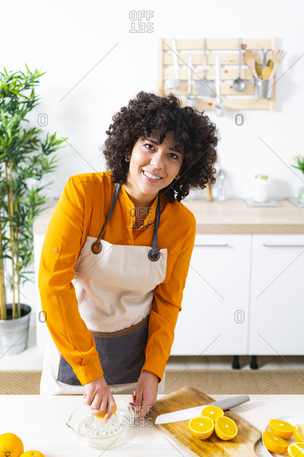 Young woman wearing apron squeezing orange for preparing juice while standing at home