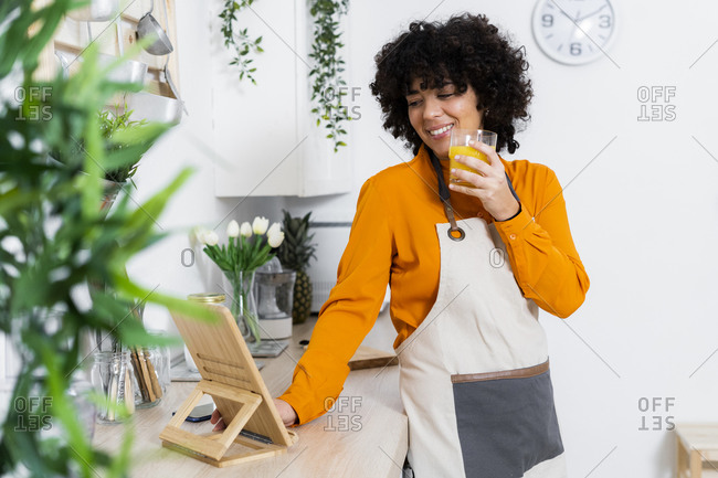 Smiling woman wearing apron drinking orange juice while using digital tablet at home