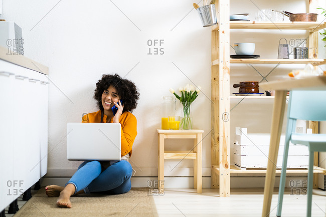 Smiling young woman with laptop talking on mobile phone while sitting on floor at home