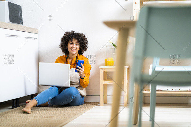 Smiling woman with laptop and mobile phone sitting on floor in kitchen at home