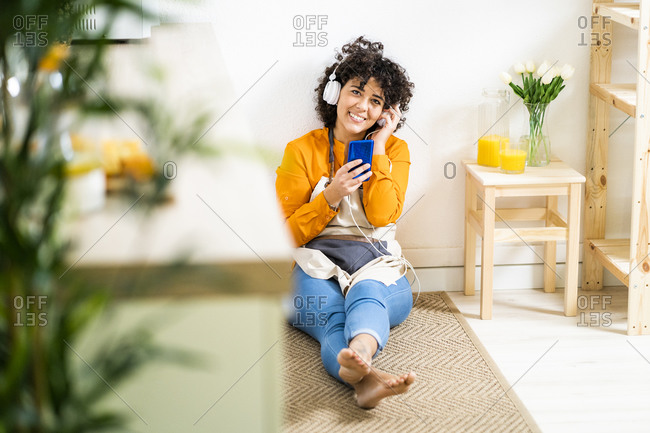 Young woman with headphones using mobile phone while sitting on floor at home