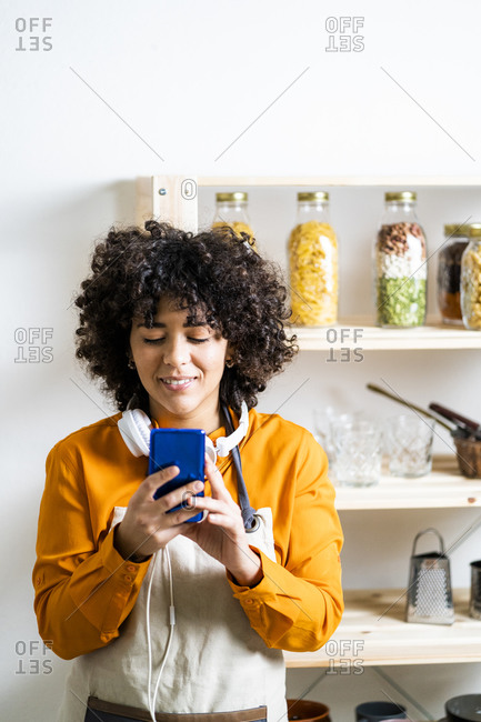 Curly hair woman using mobile phone while standing in kitchen at home