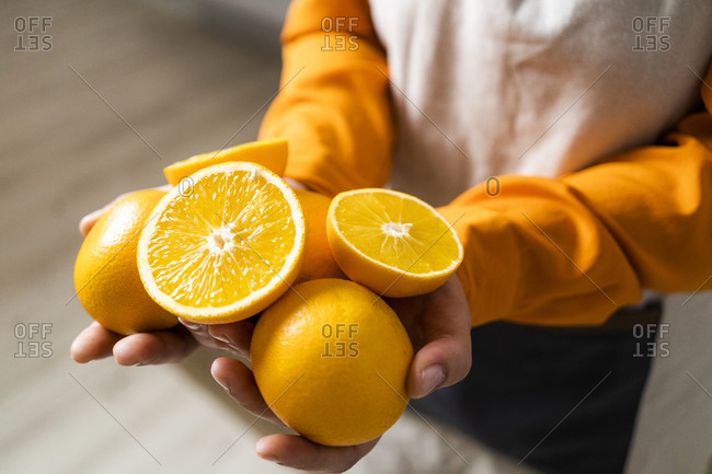 Woman holding orange and slice of orange in hand while standing at home