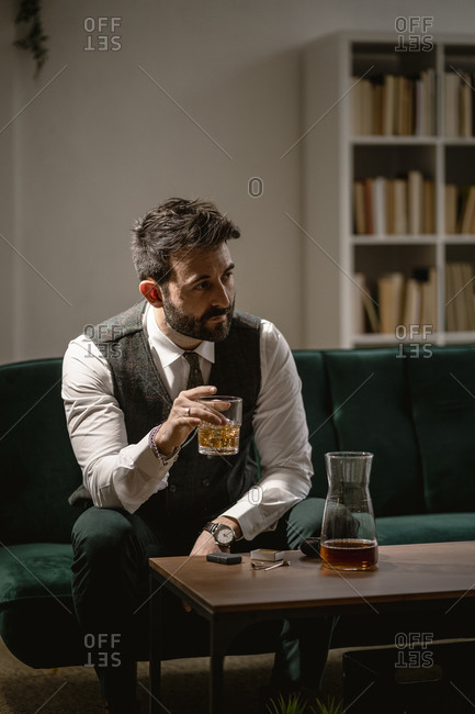 Portrait of well-dressed man drinking whiskey in living room