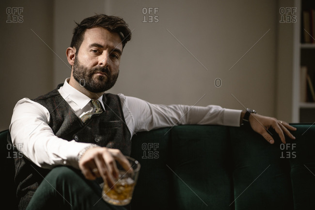 Portrait of bearded man sitting on sofa with glass of whiskey in hand