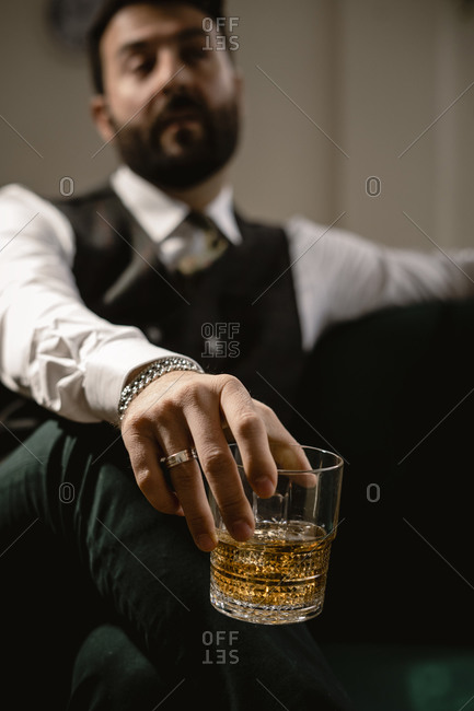 Arm of man holding glass of whiskey