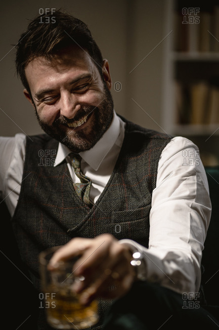 Portrait of bearded man laughing while enjoying glass of whiskey