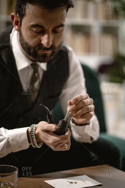 Bearded man preparing smoking pipe