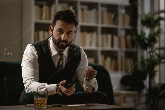 Portrait of bearded man preparing smoking pipe
