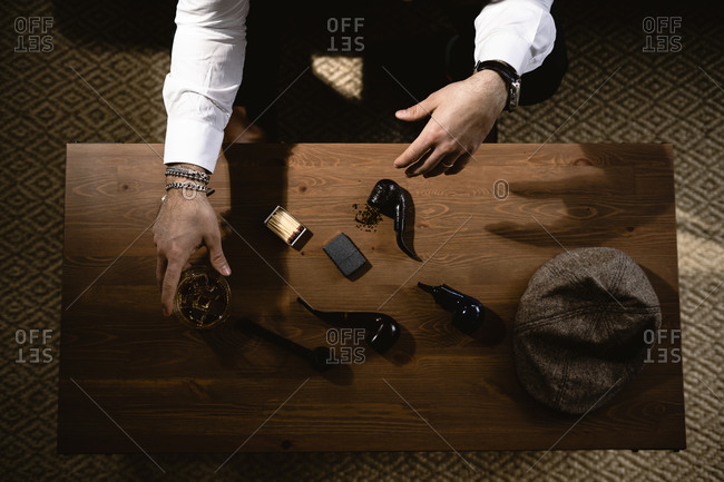 Hands of man preparing pipe at coffee table