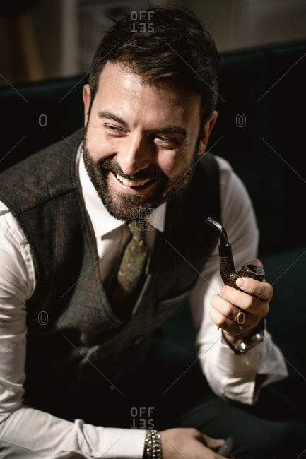 Portrait of bearded man laughing while smoking pipe