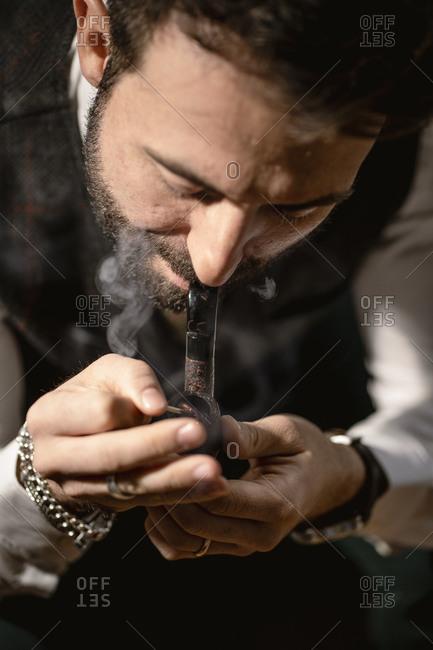 Bearded man smoking pipe alone