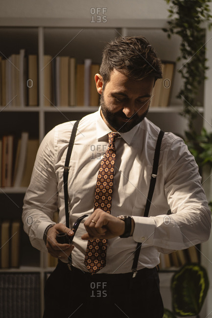 Portrait of bearded man checking time with smoking pipe in hand