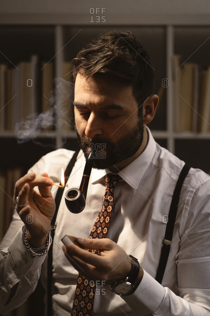 Portrait of bearded man lighting smoking pipe with match
