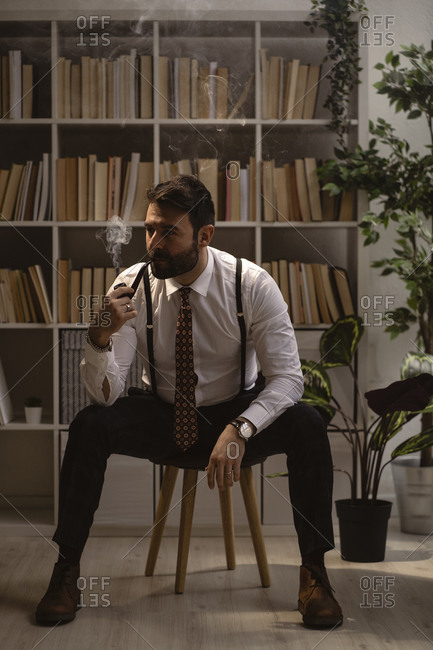 Portrait of bearded man sitting on stool and smoking pipe