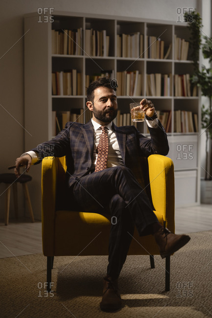 Portrait of well-dressed man sitting in armchair and enjoying cigar and glass of whiskey