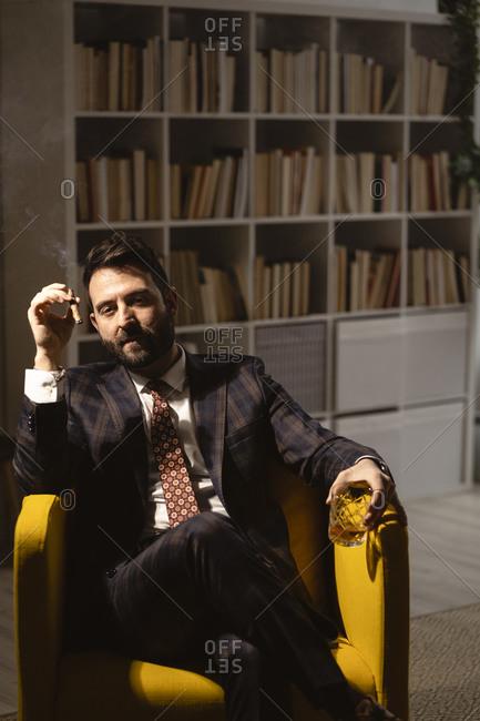 Portrait of bearded man enjoying cigar and glass of whiskey