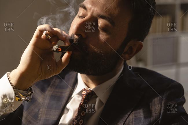 Portrait of bearded man smoking cigar