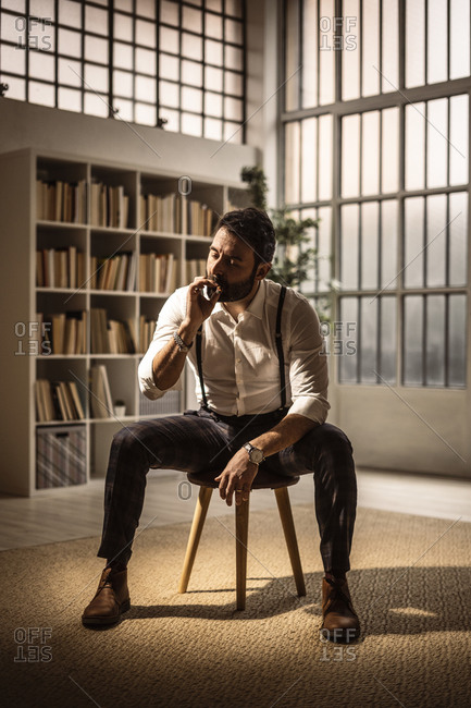 Portrait of bearded man sitting on stool and smoking cigar