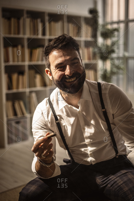 Portrait of bearded man laughing while smoking cigar