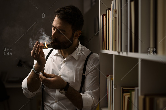 Portrait of bearded man smoking cigar in front of bookshelf