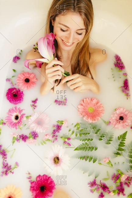 Smiling woman lying in bathtub while taking milk bath at spa