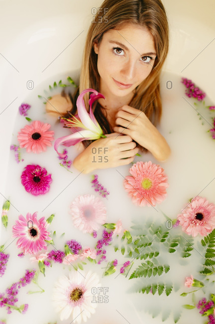 Young woman taking milk bath in bathroom