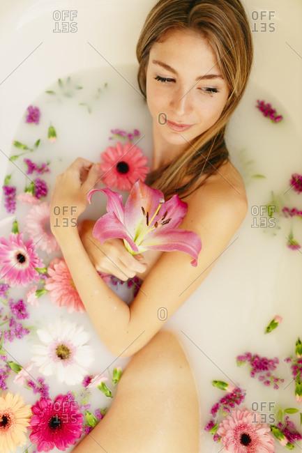 Beautiful woman looking away while taking bath in beauty spa