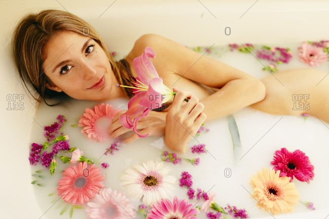 Young woman with flowers having milk bath in bathroom