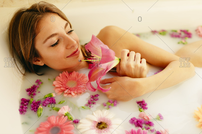 Beautiful woman relaxing while taking bath at beauty spa