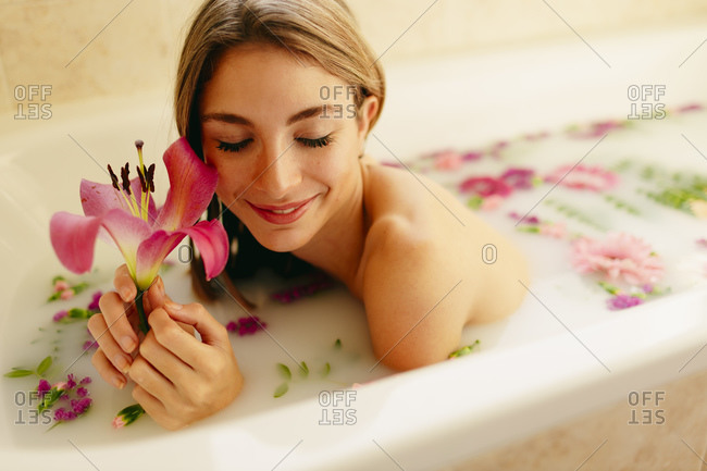 Happy woman with flowers lying in bathtub at spa