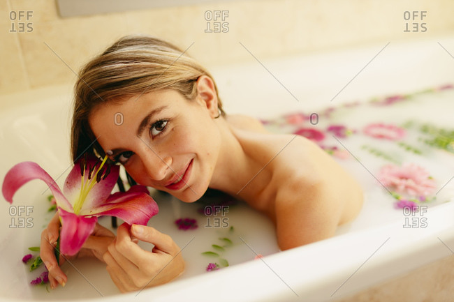 Beautiful woman smiling with flowers while lying in bathtub at beauty spa