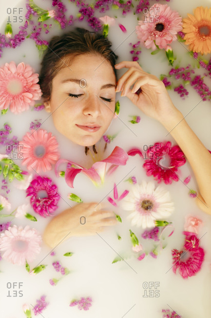 Young woman relaxing with eyes closed in bathtub at spa