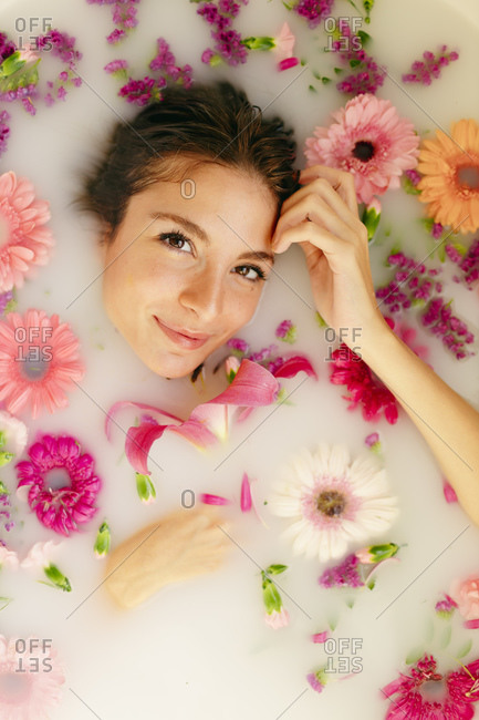Smiling woman relaxing in bathtub at beauty spa