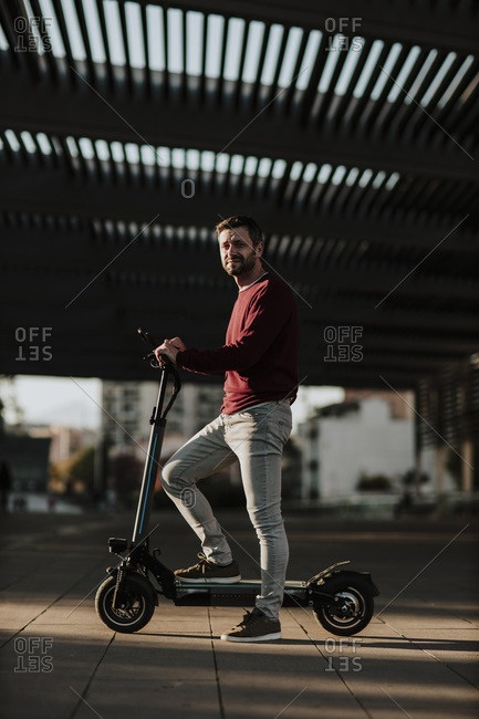 Mature man standing with electric push scooter on footpath during sunset