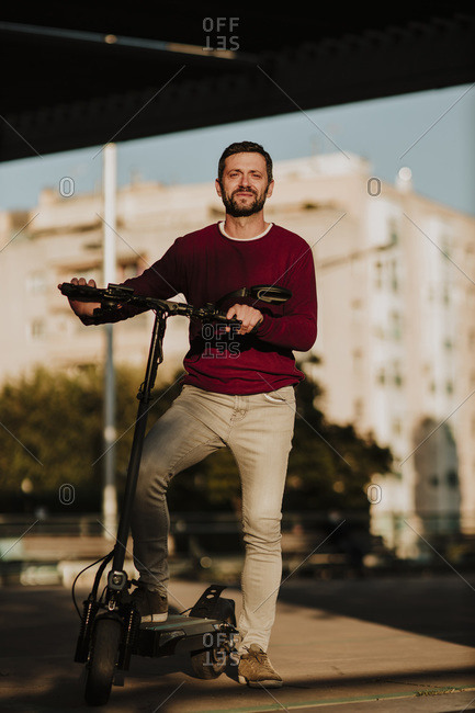 Smiling man with electric push scooter standing in city