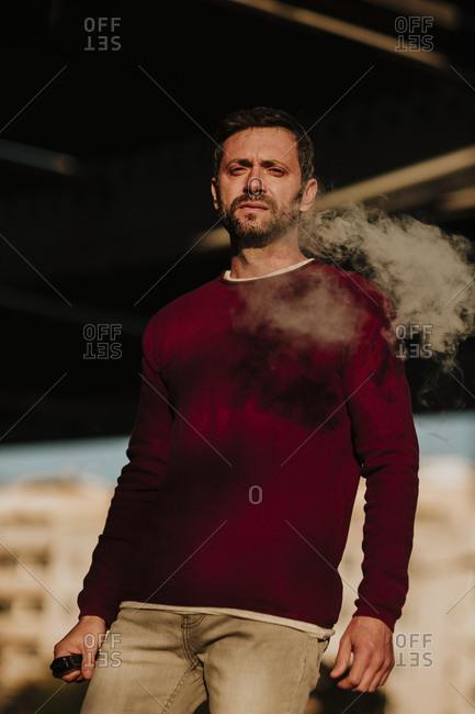 Man smoking while standing outdoors