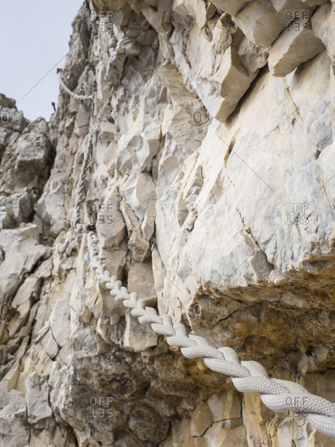 Rope hanging from steep cliff in Sexten Dolomites
